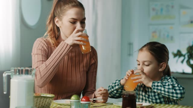mother and daughter having breakfast at home - juice drink stock videos & royalty-free footage