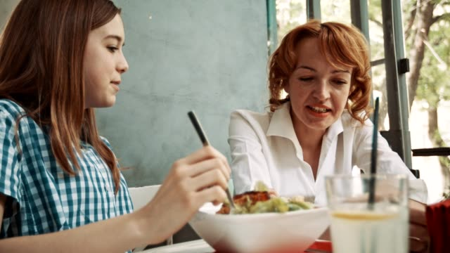 Mother and daughter having dinner in restaurant