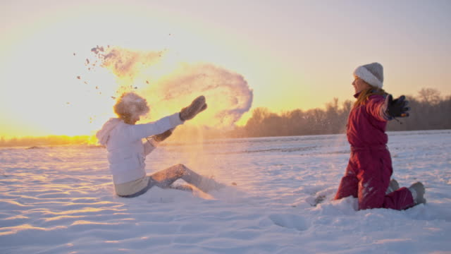 slo mo madre e figlia che si diverte nella neve - winter video stock e b–roll