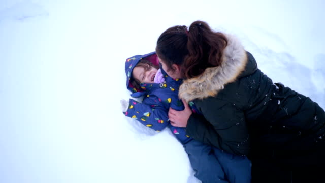 mother and daughter having fun on a winter day - fare il solletico video stock e b–roll
