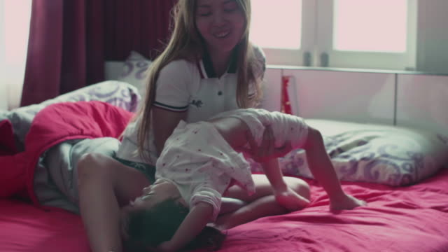 mother and daughter having fun together in bedroom - bed furniture stock videos & royalty-free footage
