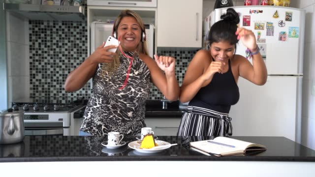 mother and daughter having fun together while dancing in the kitchen - ridere video stock e b–roll