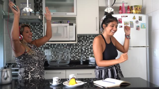 mother and daughter having fun together while dancing in the kitchen - high five stock videos & royalty-free footage