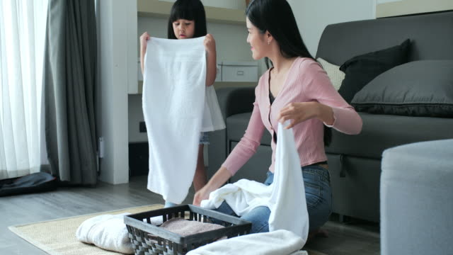 mother and daughter helper are having fun and smiling while doing laundry at home.happy asian family.day in the life of a child - laundry stock videos & royalty-free footage