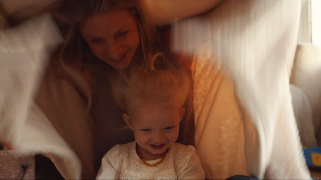 mother and daughter hiding under blanket indoors - bed sheets stock videos & royalty-free footage