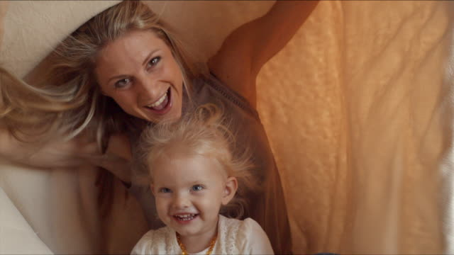 mother and daughter hiding under blanket indoors - hiding stock-videos und b-roll-filmmaterial