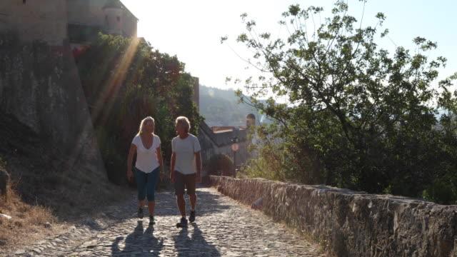 mother and daughter hike along cobblestone path, above village - kullersten bildbanksvideor och videomaterial från bakom kulisserna