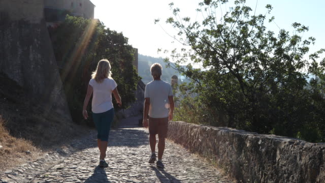 mother and daughter hike along cobblestone path, above village - escapism stock videos & royalty-free footage