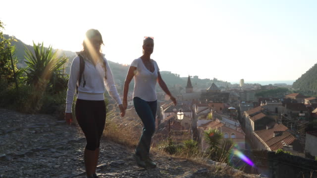 mother and daughter hike along cobblestone path, above village - liguria stock videos & royalty-free footage