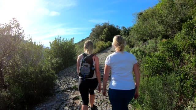 mother and daughter hike along cobblestone track, in hills - daughter stock videos & royalty-free footage