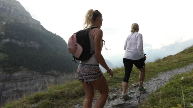mother and daughter hike along mountain pathway - climbing equipment stock videos & royalty-free footage