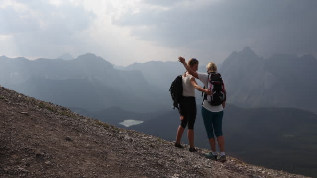 mother and daughter hike along ridge crest - alleinerzieherin stock-videos und b-roll-filmmaterial