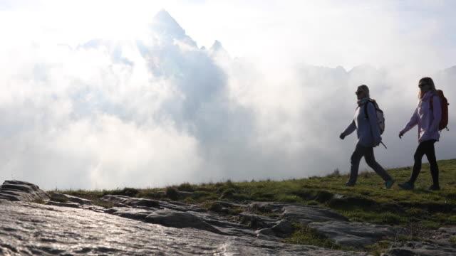 stockvideo's en b-roll-footage met moeder en dochter wandelen door bergweide - minder dan 10 seconden