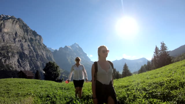 mother and daughter hike through mountain meadow - ponytail stock videos & royalty-free footage