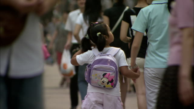 a mother and daughter hold hands as they walk along a busy sidewalk. available in hd. - two generation family stock videos & royalty-free footage