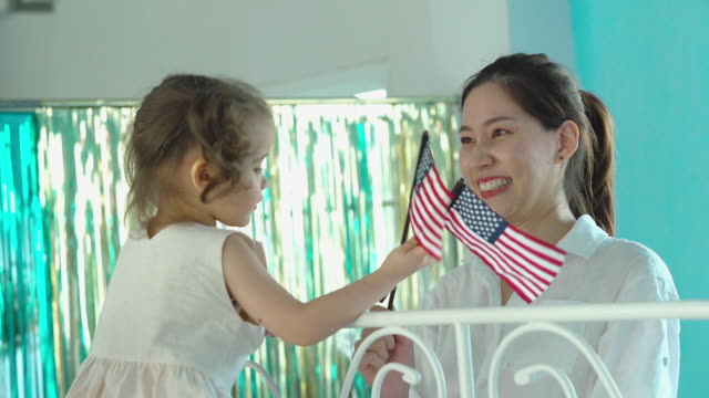 mother and daughter holding american flag and playing peekaboo game together , homeschooling concept - peekaboo game stock videos & royalty-free footage