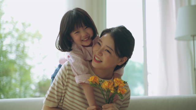 mother and daughter holding flowers and playing together on the sofa - kindertag stock-videos und b-roll-filmmaterial