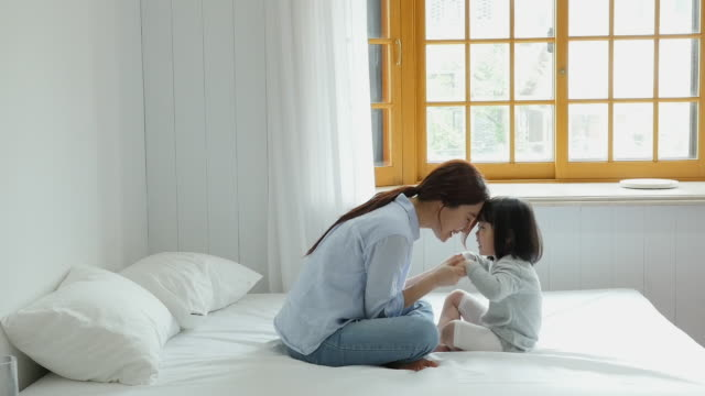 mother and daughter holding hands and playing together on the bed - daughter stock videos & royalty-free footage