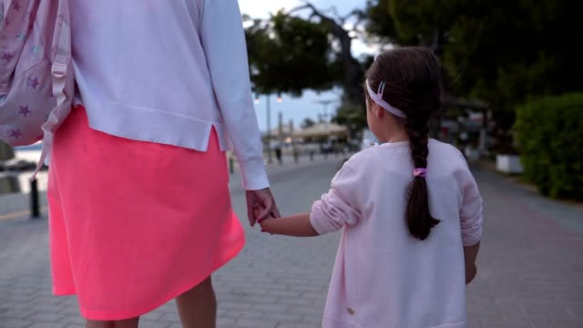 mother and daughter holding hands while enjoying relaxing walk in dusk near sea - rucksack stock videos & royalty-free footage