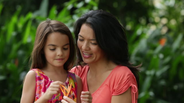 MS Mother and daughter hugging and looking at flower