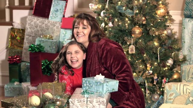 mother and daughter hugging by christmas tree - tree hugging stock videos & royalty-free footage