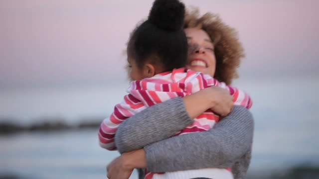 CU SELECTIVE FOCUS Mother and daughter (4-5) hugging on Virginia Beach / Virginia, USA