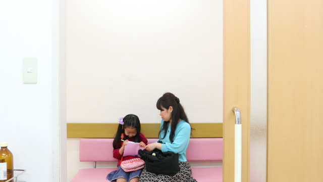 mother and daughter in a hospital waiting room - outpatient care stock videos & royalty-free footage