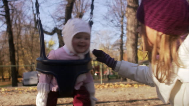 mother and daughter in a playground sweden. - cap hat stock videos & royalty-free footage