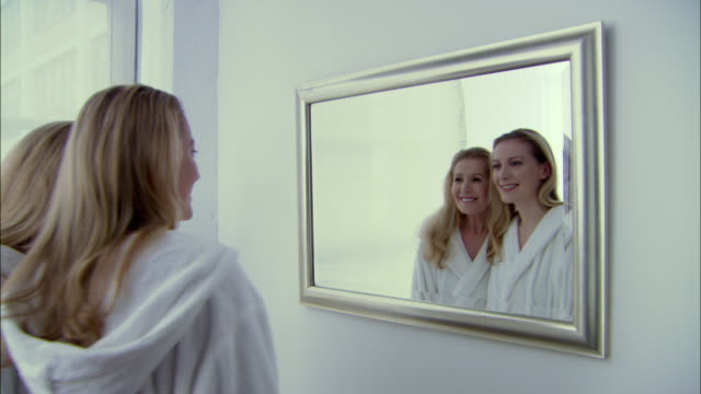 MS Mother and daughter in bathrobes walking up to mirror, looking at reflections, smiling, and laughing/ England
