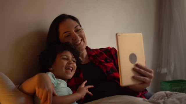 vídeos de stock, filmes e b-roll de mãe e filha na cama fazendo uma chamada de vídeo em tablet digital - equipamento de mídia