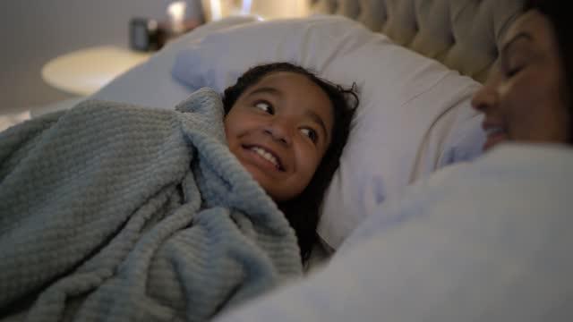 stockvideo's en b-roll-footage met moeder en dochter in bed die thuis spreken - dochter