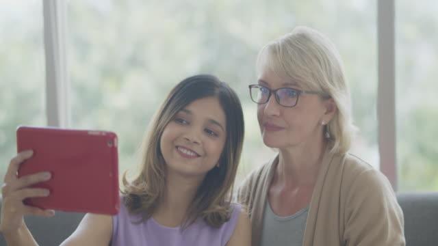 法律で母と娘は、話のための生活と寝室に滞在し、ビデオ通話のためにラップトップを使用しました.ミックススキンファミリー。 - 義母点の映像素材/bロール
