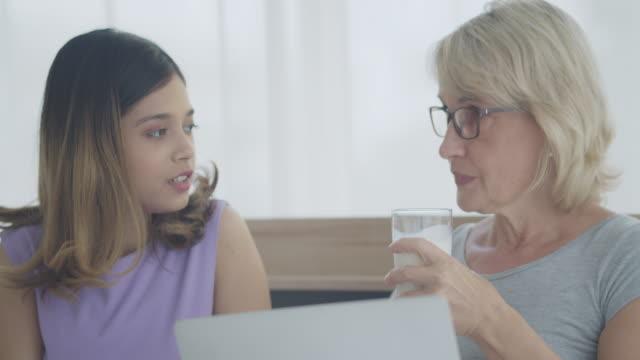 法律で母と娘は、話のための生活と寝室に滞在し、ビデオ通話のためにラップトップを使用しました.ミックススキンファミリー。母乳を飲む母。 - 義母点の映像素材/bロール