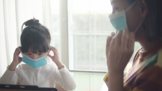 mother and daughter in medical face protection mask - multitasking mum stock videos & royalty-free footage