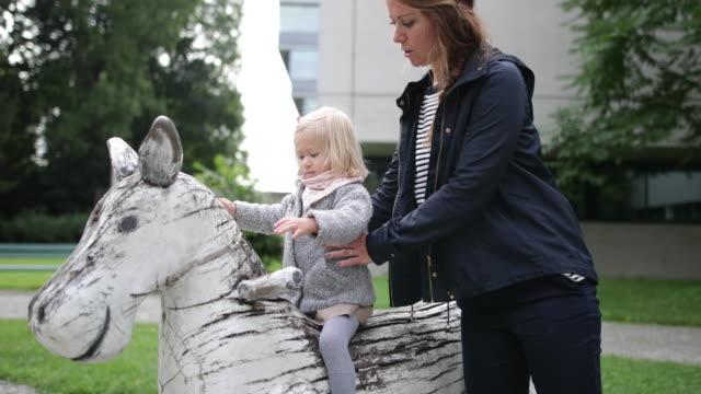 vídeos y material grabado en eventos de stock de mother and daughter in playground playing - cámara en mano