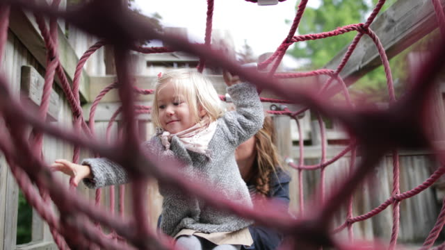 mother and daughter in playground playing - mid length hair stock videos & royalty-free footage