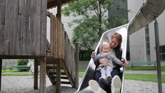 stockvideo's en b-roll-footage met mother and daughter in playground playing - glijbaan speeltuintoestellen