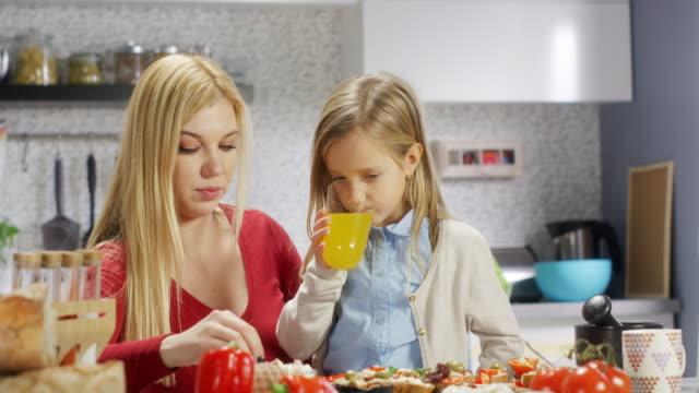 vídeos de stock, filmes e b-roll de mãe e filha na cozinha - alimentando