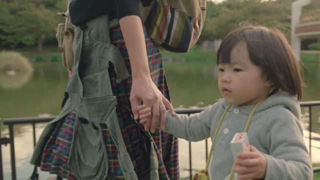 vidéos et rushes de mère et fille dans le parc. - étang