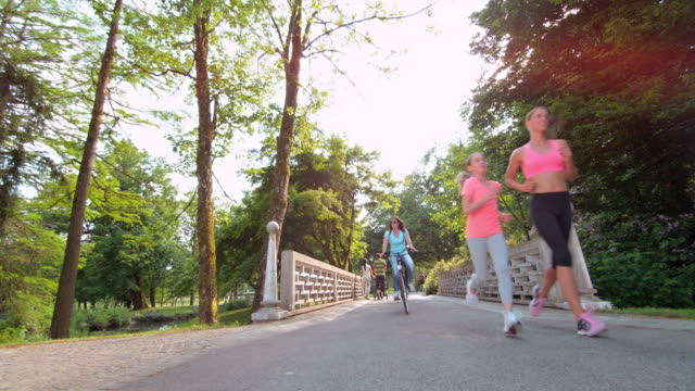 stockvideo's en b-roll-footage met ds moeder en dochter joggen over een brug in het park - footpath