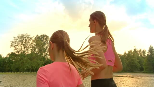 vídeos de stock e filmes b-roll de slo mo ts mãe e filha jogging na luz do sol - camisetas