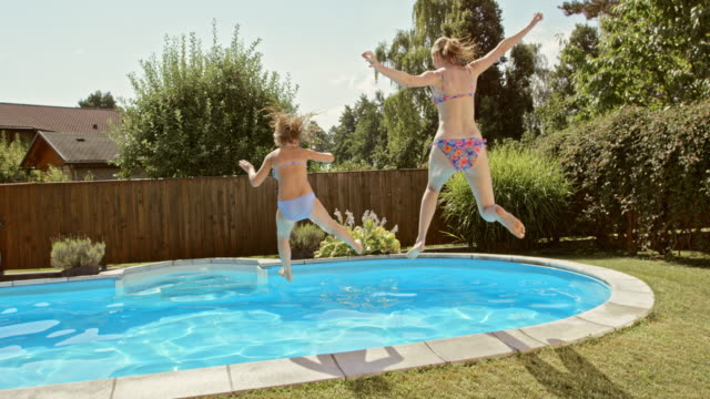slo mo cs mother and daughter jumping into the pool on a summer day - family with one child stock videos & royalty-free footage
