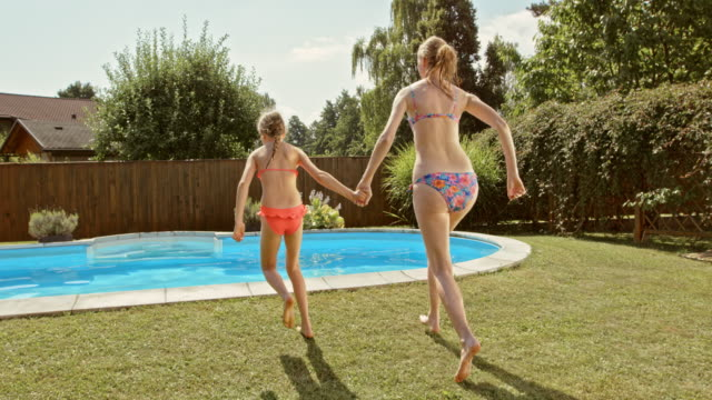 SLO MO CS Mother and daughter jumping into the pool