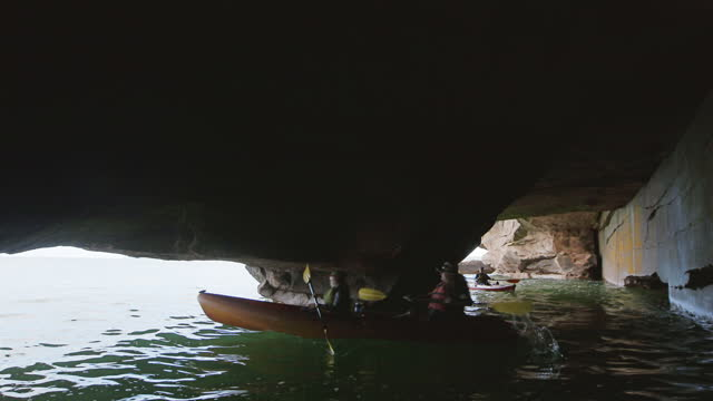 Mother and daughter kayak through sea cave as son follows behind and pumps paddle in the air excitedly.