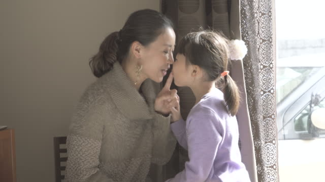 mother and daughter kissing and laughing together - いたずら点の映像素材/bロール