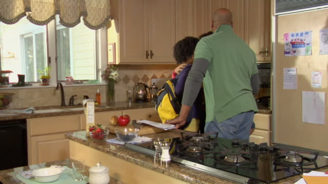 MS Mother and daughter kissing good-bye to father and son in kitchen / White Plains, New York, USA