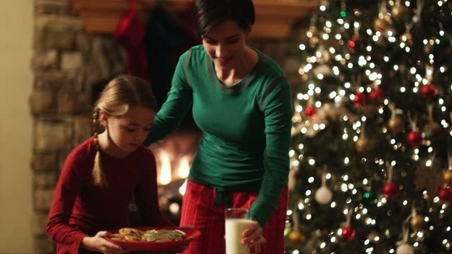 vídeos de stock, filmes e b-roll de mother and daughter leaving milk and cookies for santa claus - orem