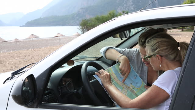 Mother and daughter look at road map inside car, on beach