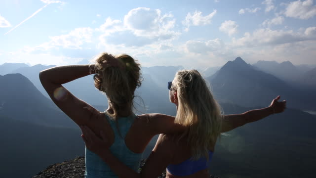 mother and daughter look off from mountain summit, exhilarated - older woman fun stock-videos und b-roll-filmmaterial