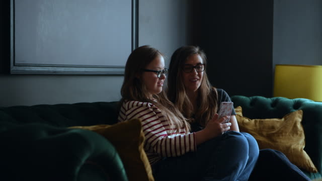 mother and daughter looking at phone whilst video calling - erwachsene kinder stock-videos und b-roll-filmmaterial